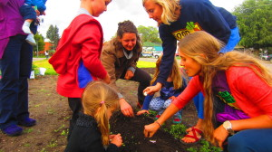 FoodCorps Service Members past and present planting garlic with children